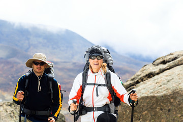 Couple trekkers hiking in mountains