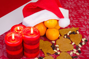 Christmas composition with orange, candles and cakes