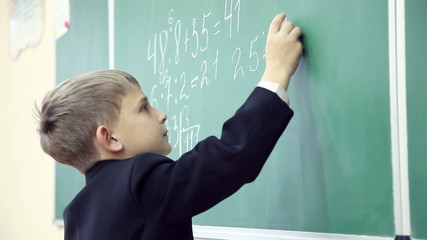 little boy solves math on the blackboard at school 8