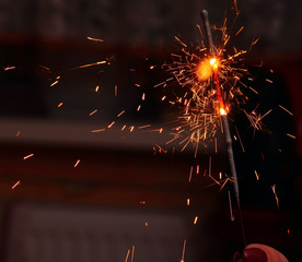 Child's hand, holding a burning sparkler