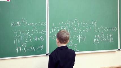 little boy solves math on the blackboard at school 1