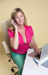 Secretary sitting in office chair working at her desk