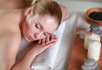 Beautiful young woman getting spa massage, lying on salon