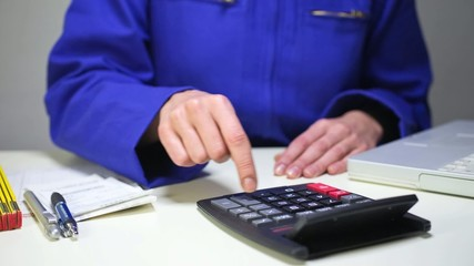 workshop manager typing on calculator