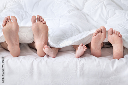 Feet of a family sticking out from the white quilt - 74347939