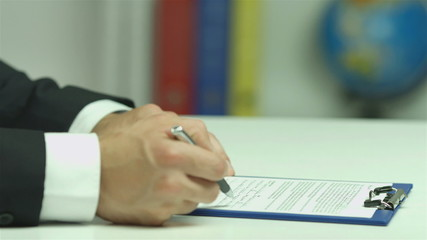 The european businessman read and sign the contract papers