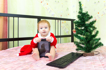 Pleased baby in new year suit with tablet computer