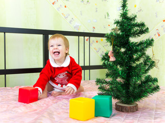 Laughing boy playing with bricks near new year fir
