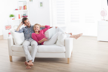 couple relaxing on a couch and using a laptop