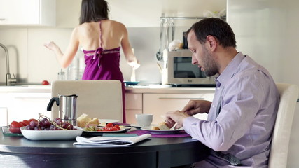 Man talking while his wife serving  him breakfast in the kitchen