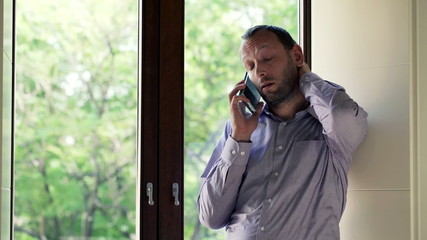Sad, trouble man talking on cellphone by the window