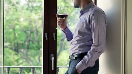 Sad, pensive man drinking wine and looking out the window