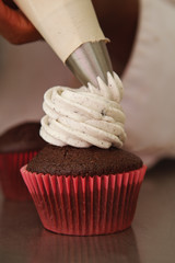 Cookies and cream cupcake being frosted