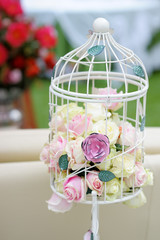 White cage with natural roses