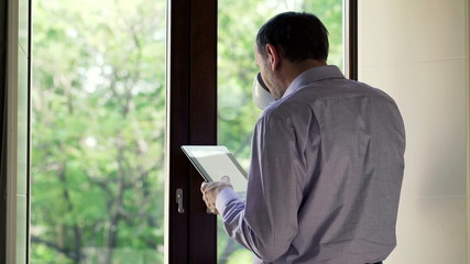 Man drinking tea and reading tablet  by the window
