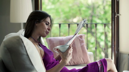 Woman drinking tea  reading news on tablet by the window