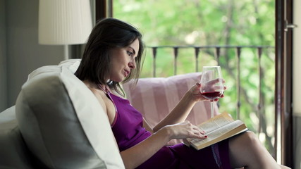 Young woman drinking wine and reading book on sofa at home