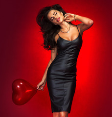 Lovely brunette woman with heart balloon.