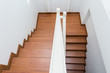 wooden staircase made from laminate wood in white modern house - 74353535