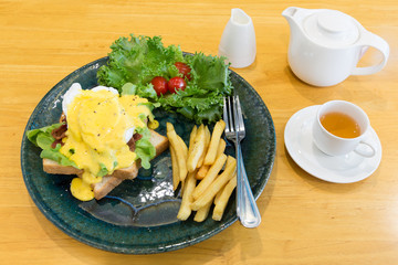 Egg Benedict serve with french fries and hot tea