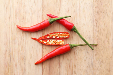 Red chilli peppers on wooden surface