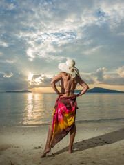 Woman with sarong on the beach at sunset