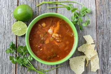 Tortilla Soup with Chips, fresh lime and cilantro on Rustic Wood