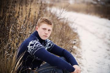 sad boy sitting at winter road