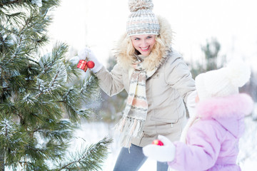 Happy mother and child playing with christmas tree decorations