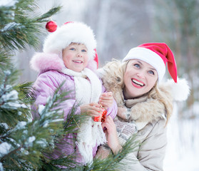 Happy mother and kid in Santa's hats with christmas tree