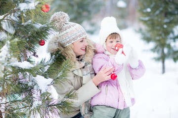 Happy parent and kid playing with christmas tree decorations
