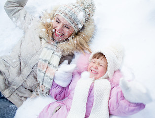 Happy parent and kid lying on snow in winter outdoor