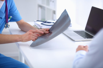 Portrait of a smiling male doctor with laptop sitting at desk in