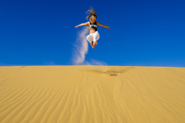 girl jumping on the yellow sand dune