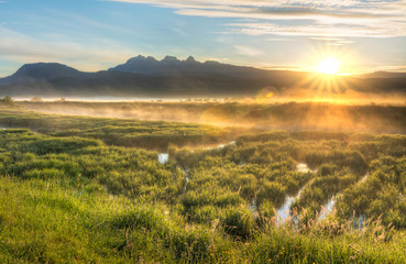 Sun Star Over Mountains With Misty Bog