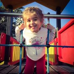 Bambina al parco che gioca e sorride