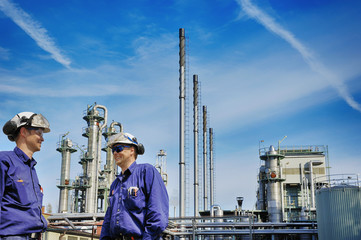 oil workers in front of large chemical refinery