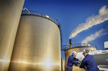 oil gas and workers with large industrial storage tanks