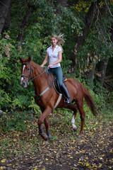 Joyful girl riding horse in forest
