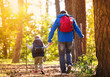 Father and son walking in autumn forest - 74367368