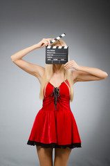Woman with movie board wearing red dress