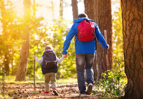 Leinwanddruck Bild Father and son walking in autumn forest