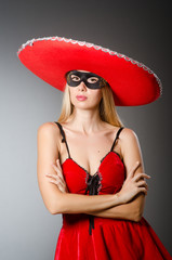 Woman wearing red sombrero and mask