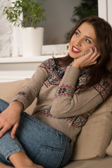 Young happy woman sitting on the sofa at home while talking on p