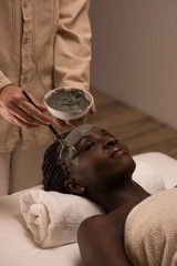 African woman having clay facial mask