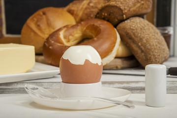 Gekochtes Ei auf dem Frühstückstisch, Bagel,Brötchen und Butter