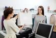 Leinwanddruck Bild - Happy customer with shopping bag in fashion showroom