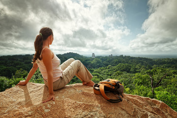 Young woman with a backpack is looking at ruins maya Tikal