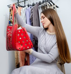 Young woman choosing bag in a showroom