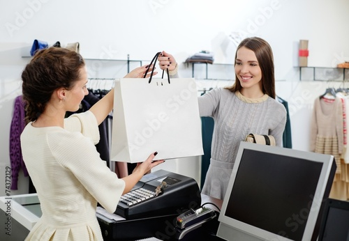 Leinwanddruck Bild Happy customer with shopping bag in fashion showroom